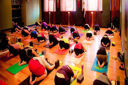 People crouched over on yoga mats.