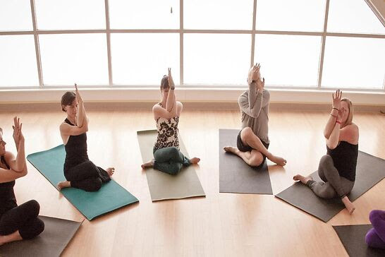 Five people with crossed arms and legs sitting on yoga mats.