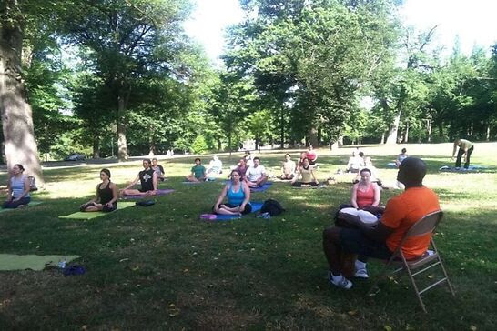 People doing yoga in a park.
