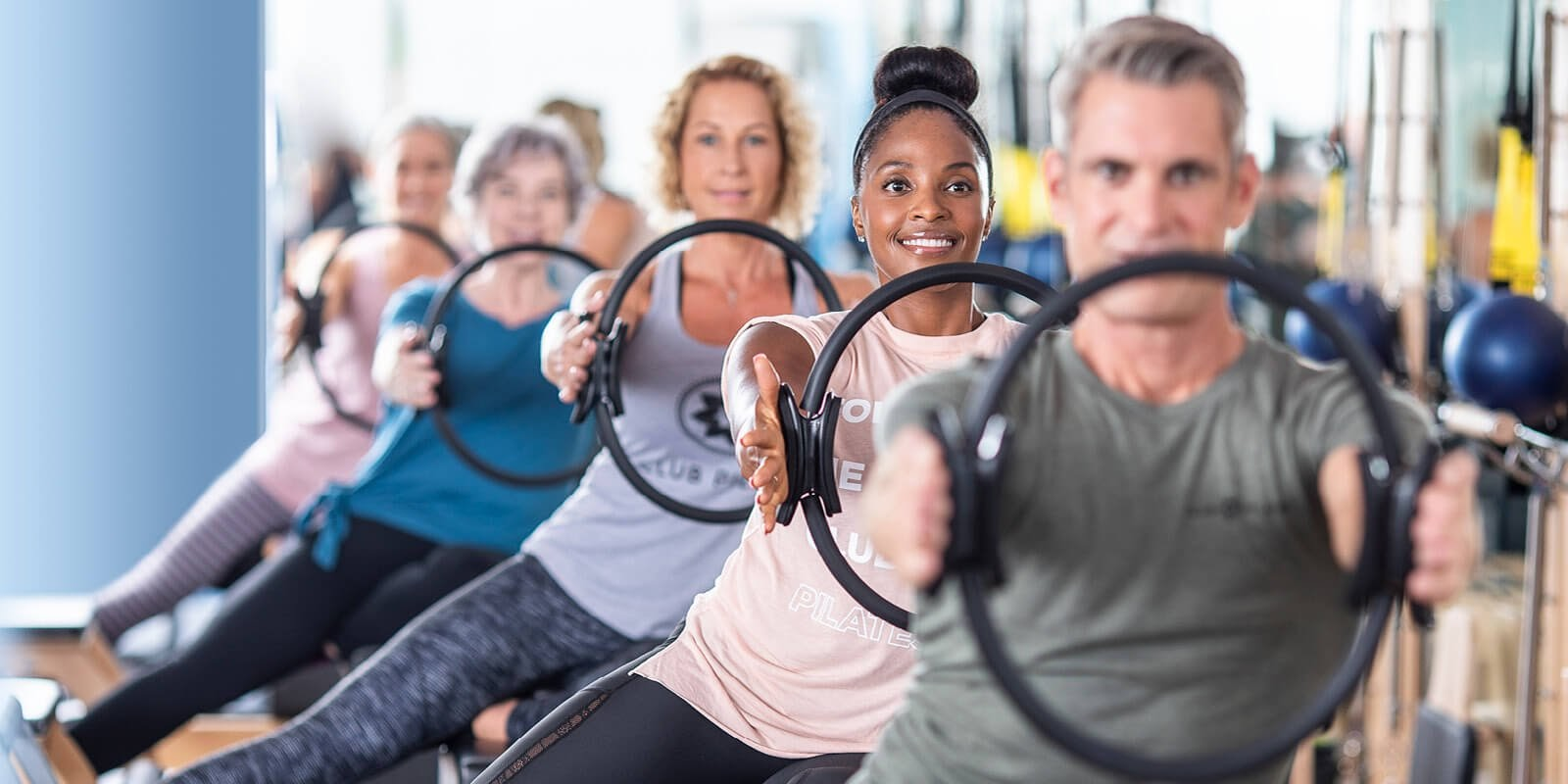 A line of people using pilates equipment for their arms.