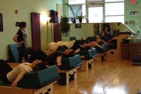 Five people laying on pilates machines while a teacher instructs them.