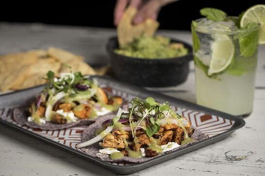 Two chicken tacos topped with onions next to a glass of lime water and guacamole.