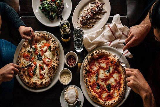 Two people slicing into their own pizzas next to drinks and sides.