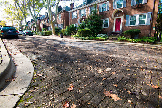 A wooden street surrounded by brick row houses.