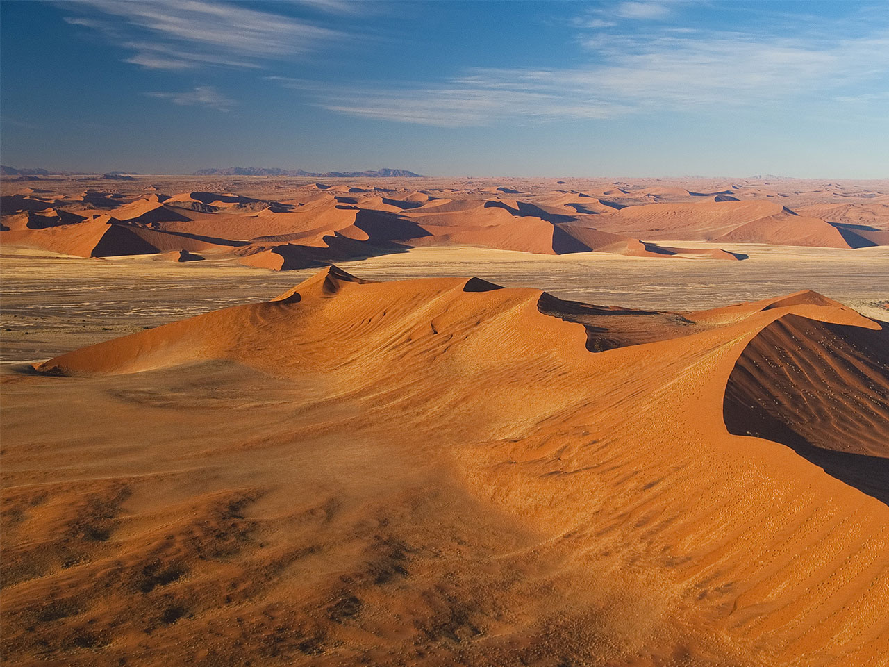 An aerial view over the vast sand dunes of the Namib Desert.