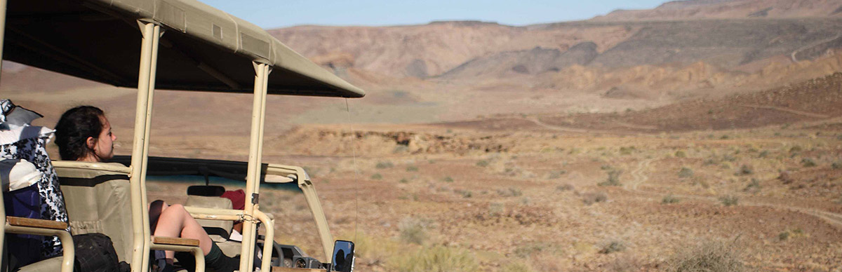 A close up of an open safari vehicle on a drive in the harsh and dry mountainous landscape of Damaraland.
