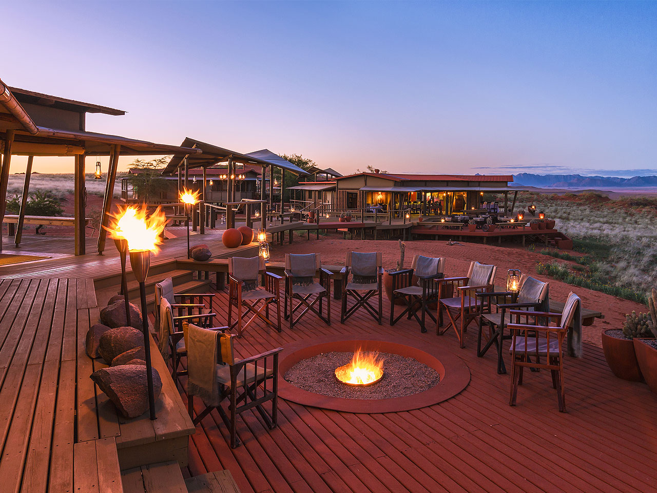 View of the fire pit, deck and main area of Wolwedans Dunes Lodge at dusk.