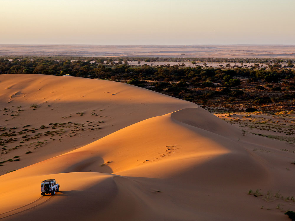An aerial view of a land cruiser on a sand dune of the Namib Desert overlooking the dry Swakopmund riverbed.