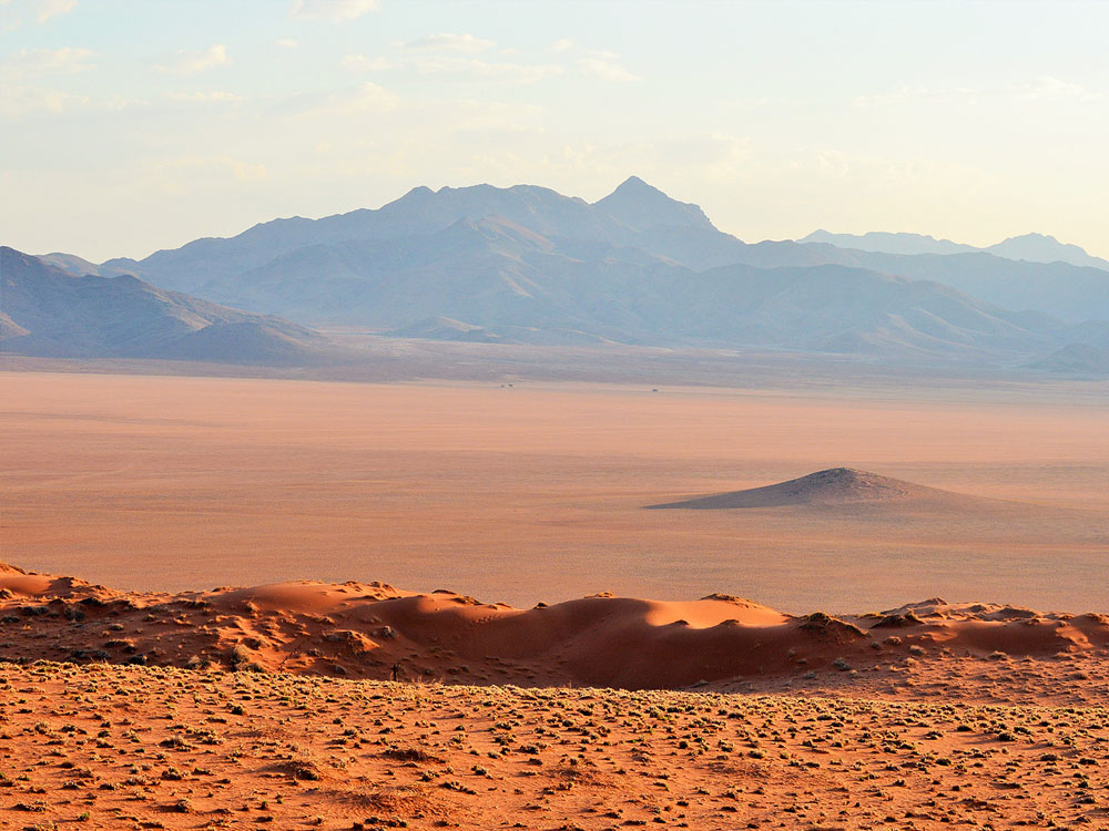 An endless landscape of the Namib Desert from a red sand dune overlooking an open plain and the distant mountains.
