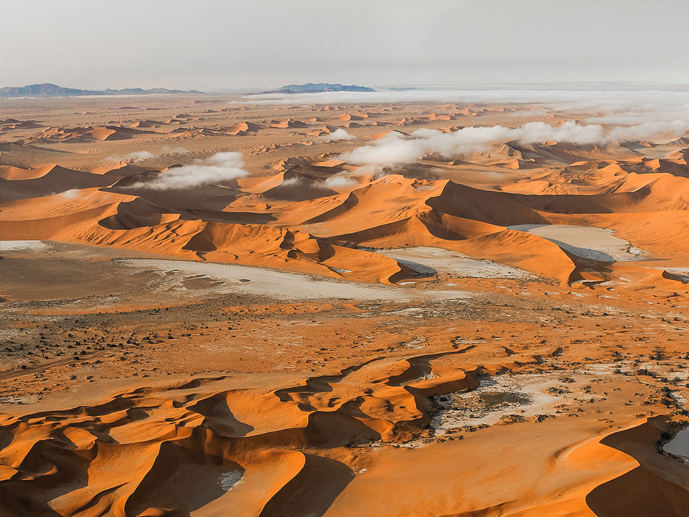 An aerial view from above scattered clouds over the endless sand dunes of the Namib Desert.