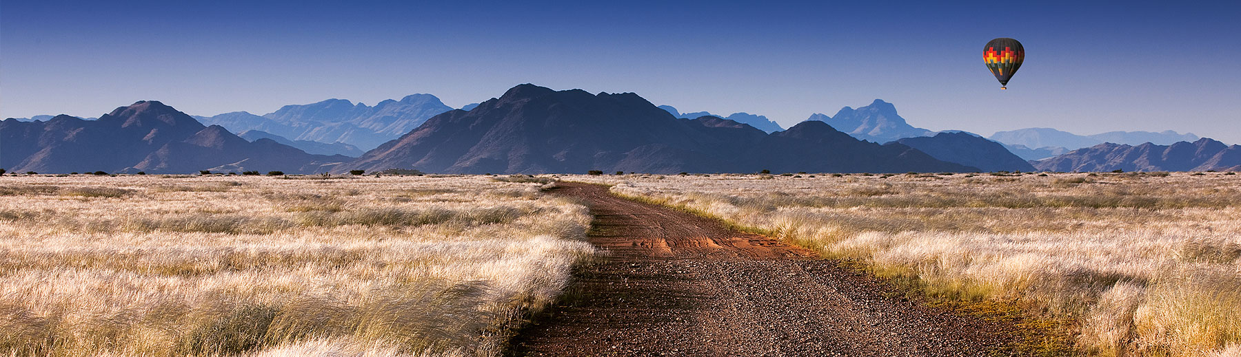 A panoramic view of a dirt road through a grass plain with a colourful hot air balloon floating in the distance near the mountains.