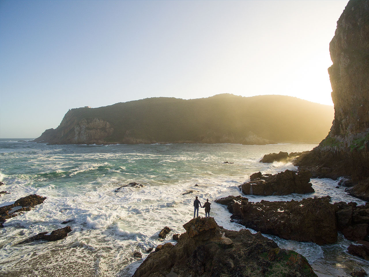 Two people holding hands on the rocks in the shore break at the base of the cliffs looking onto cliffs in the distance.