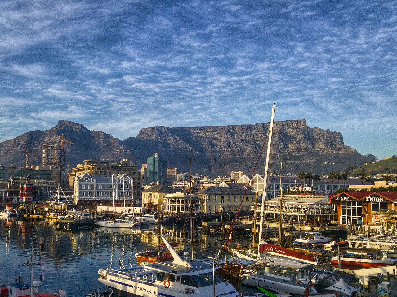 A view of Table Mountain beneath clouded blue skies over the Cape Town harbour.