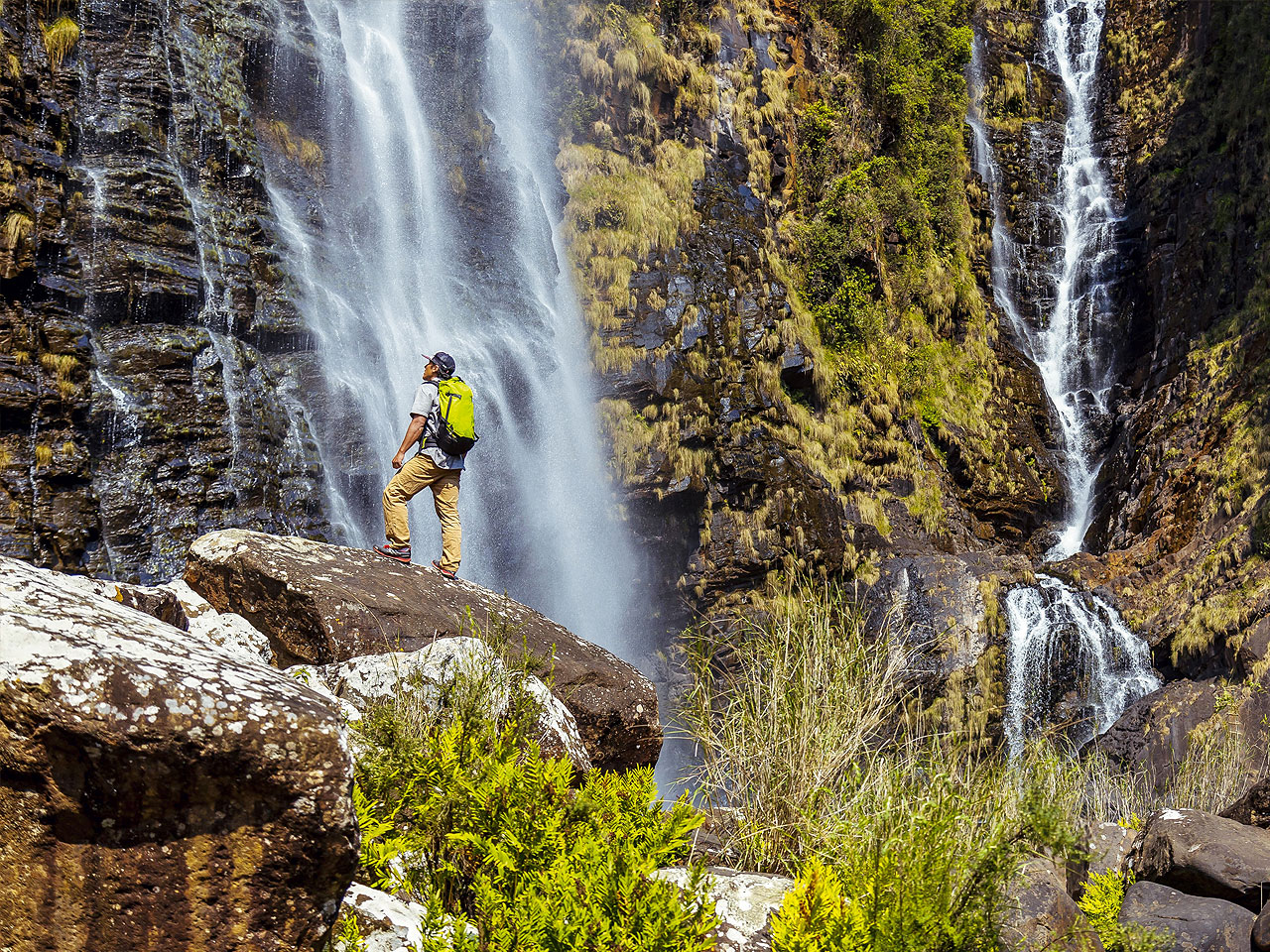 A backpacker standing on a rock at the base of a waterfall.