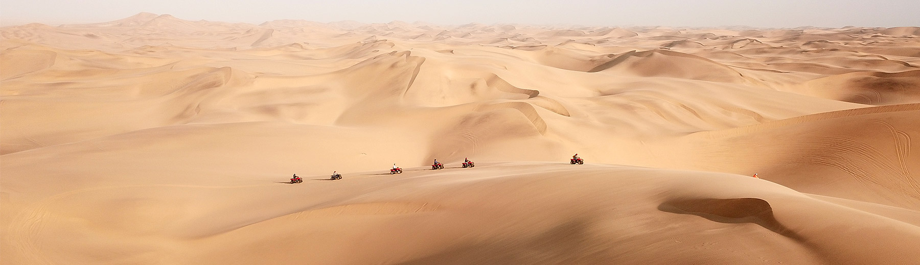 A panoramic view of quad bikes on an excursion in the endless dunes of the Namib Desert in Swakopmund.