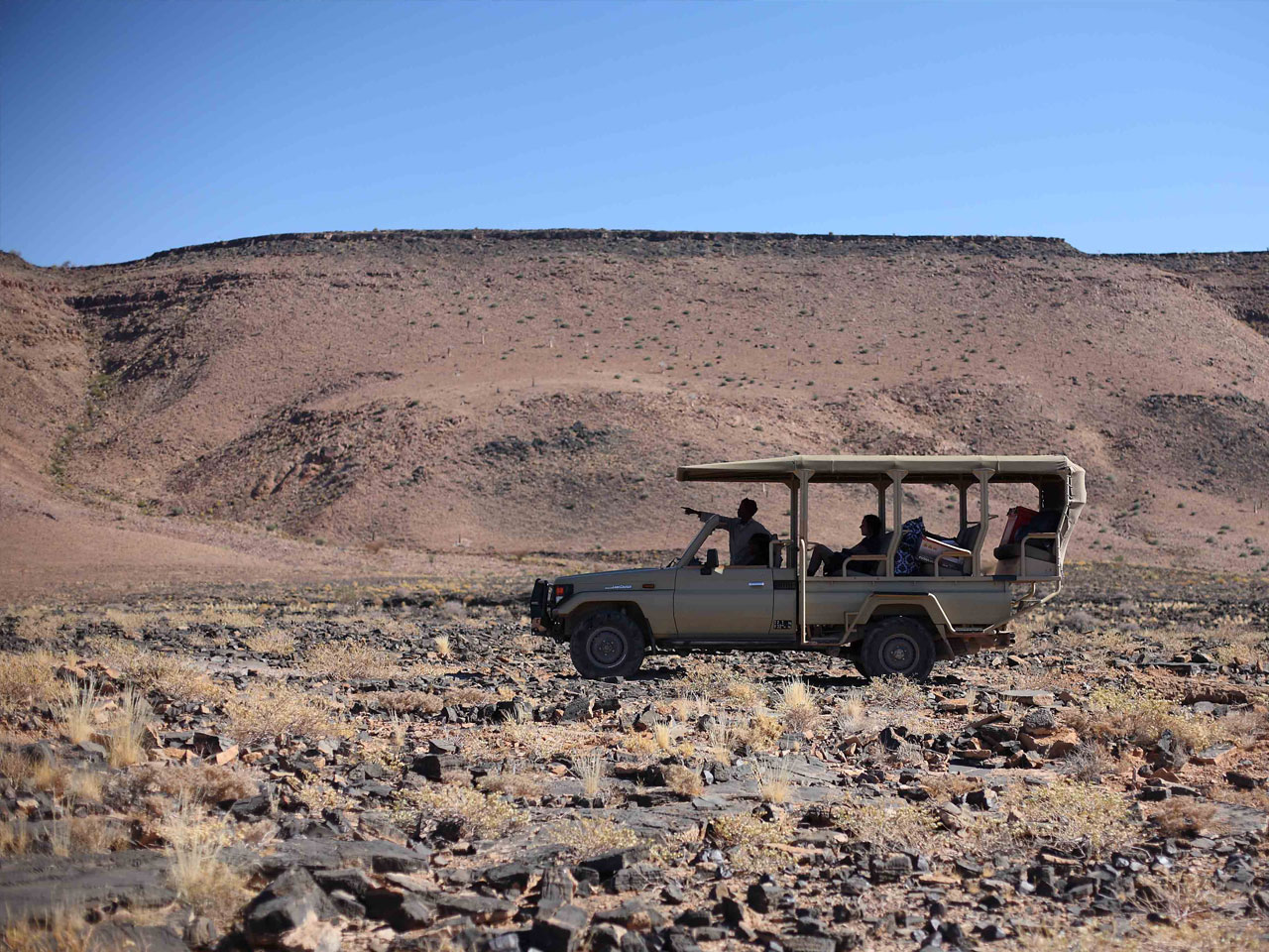 An open safari vehicle on a nature drive in the Fish River Canyon.