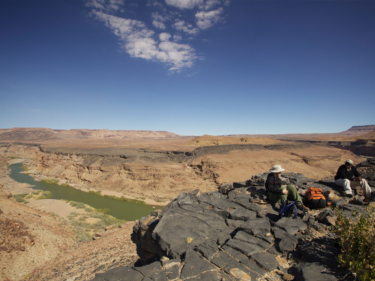 A guide and guest sitting with her backpacks on a cliff overlooking water in the Fish River Canyon below.