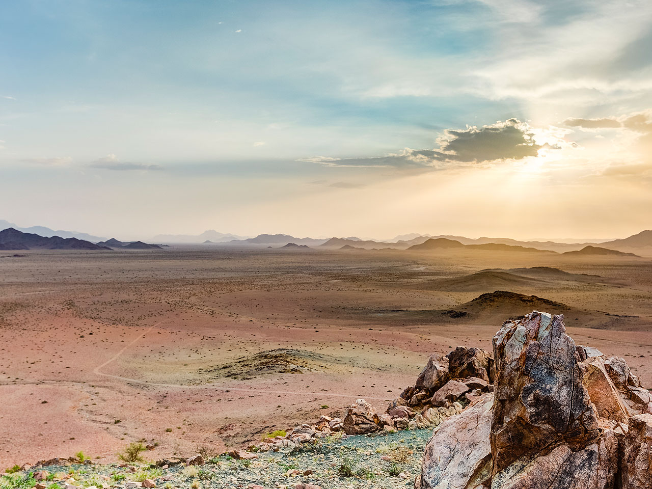 A view out over the endless plains and mountain landscape of the NamibRand Reserve at sunrise.