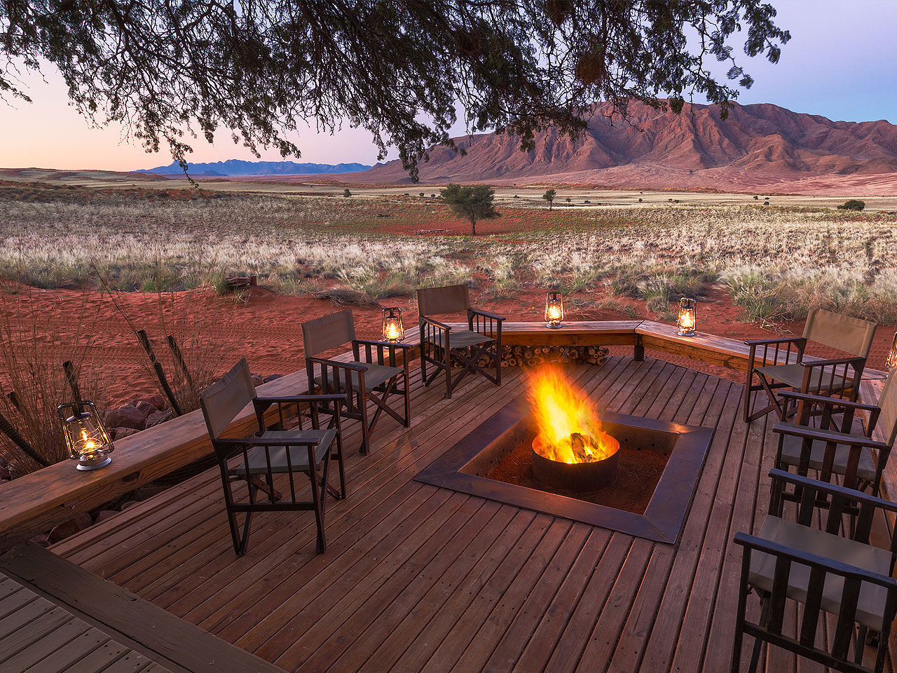 A view at sunset from the fire pit and deck at Wolwedans Dunes Camp over the waterhole and surrounding mountains.