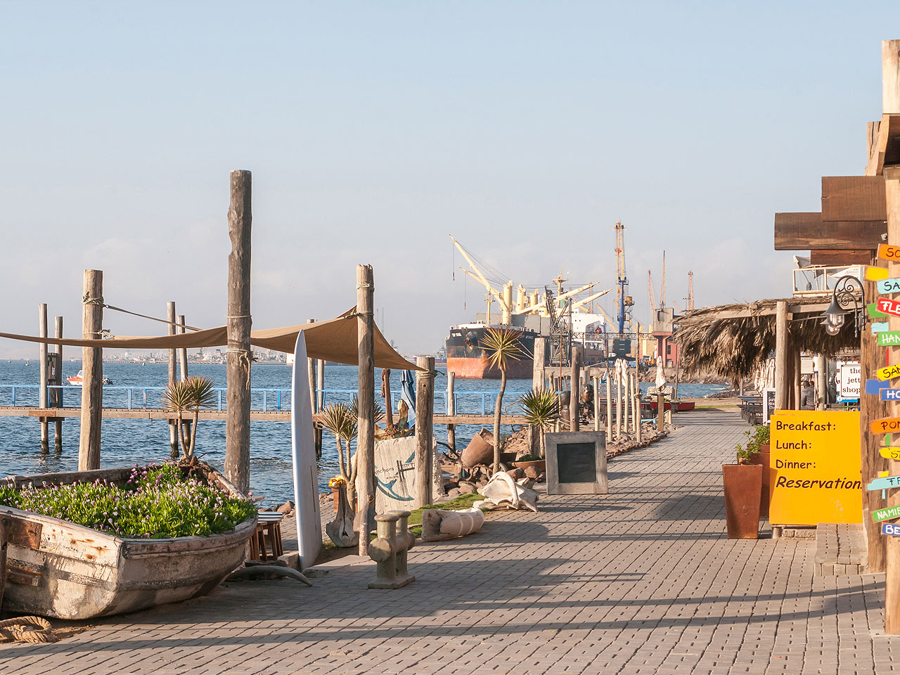 Walvis Bay Waterfront with shops and a large ship in harbour in the background.