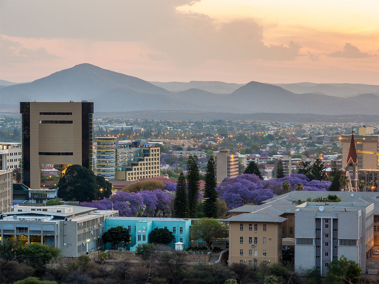 A view out over the buildings and city of Windhoek at sunset with the hills in the background.