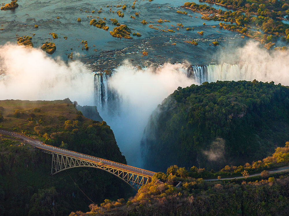 A view over the famous bridge at Victoria Falls with the falls in the background.