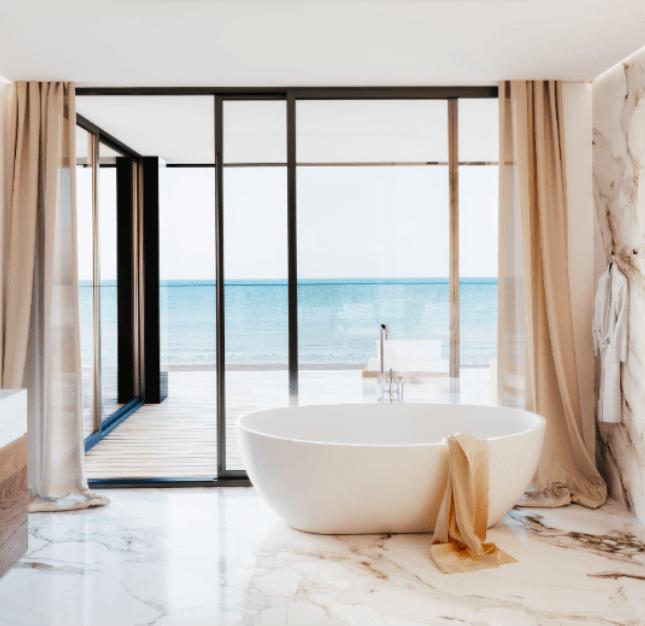 Prachtig afgewerkte badkamer aan de kust. Ovaal vrijstaand bad staat voor een grote glaspartij. Zeer veel lichtinval.
