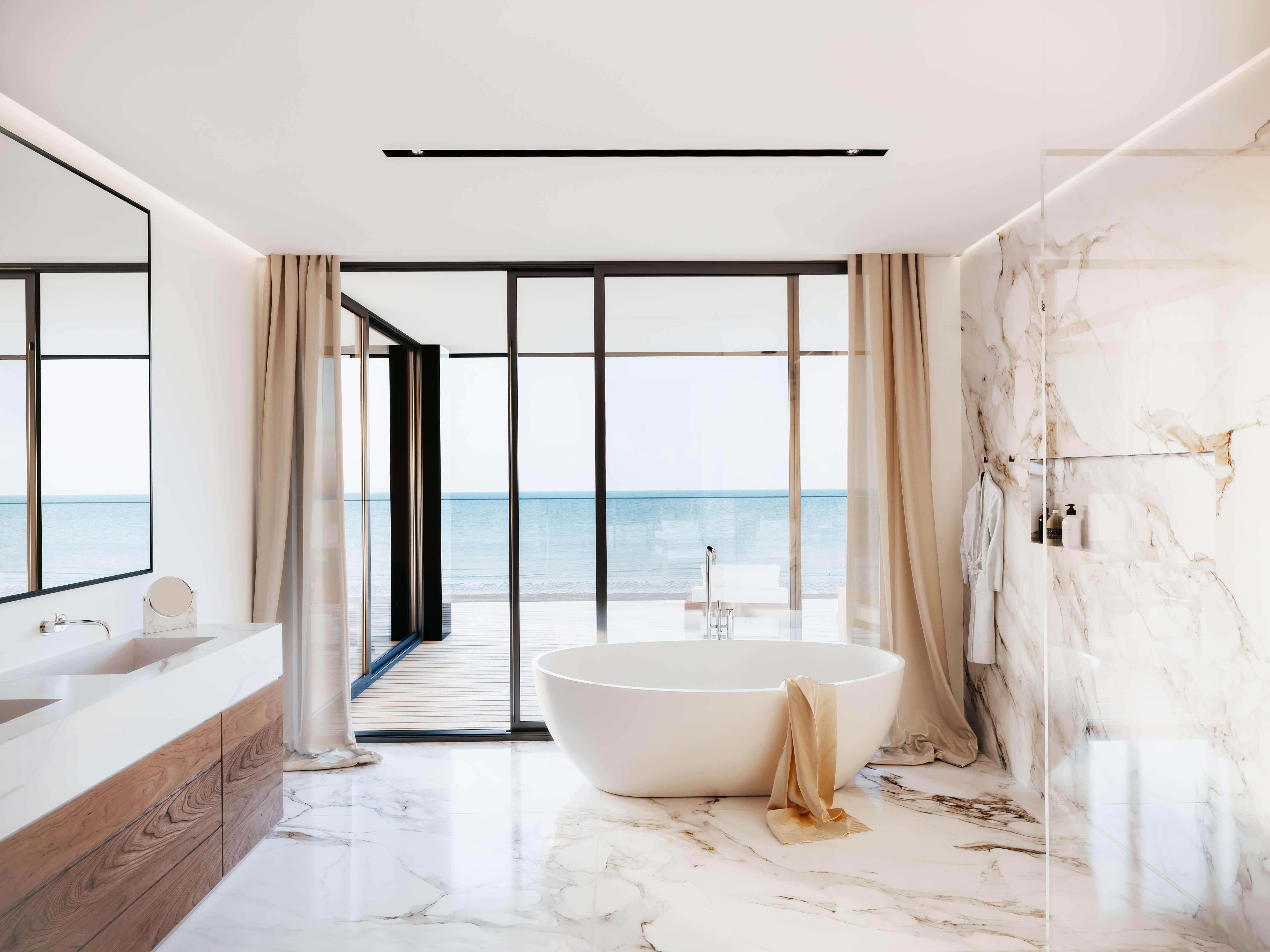 Prachtig afgewerkte badkamer. De focus ligt op het uitzicht aan de zee. Voor de grote glaspartijen staat een ovaal vrijstaand bad met een handdoek netjes gedrapeerd over de leuning. Ramen hebben een zwart profiel en zowel de rechter muur als vloer hebben een marmeren look. Straalt elegantie uit met een warm gevoel.