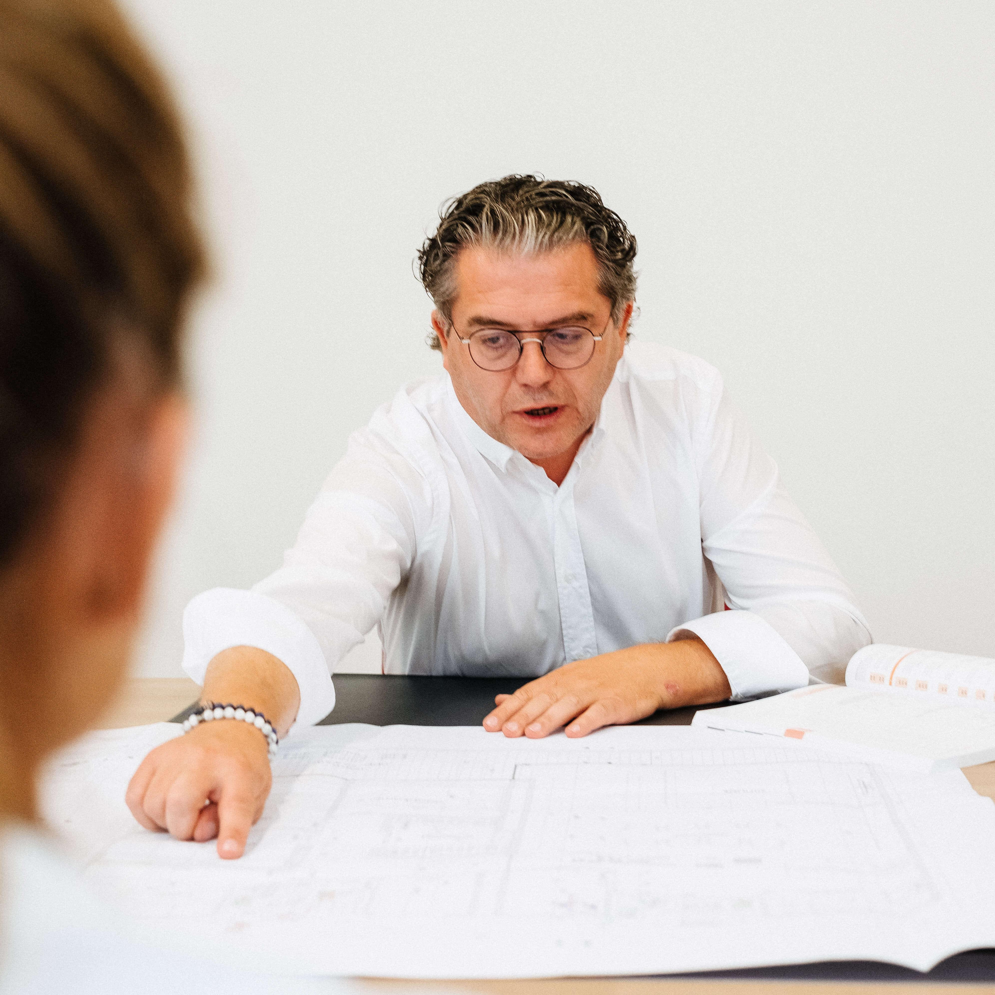 Peter Van Severen bespreekt plannen met klant.