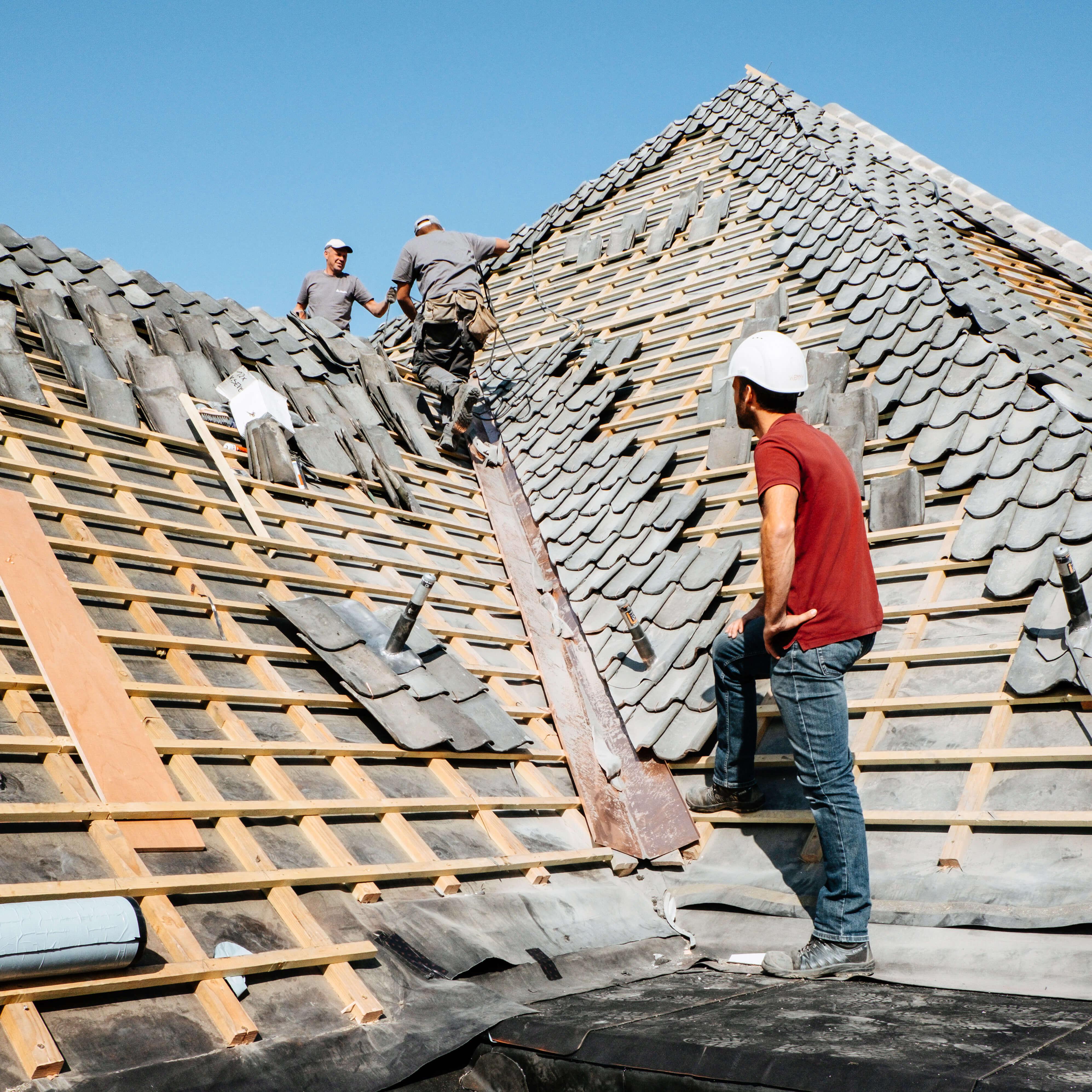 3 werknemers aan het werk bovenop een dak.