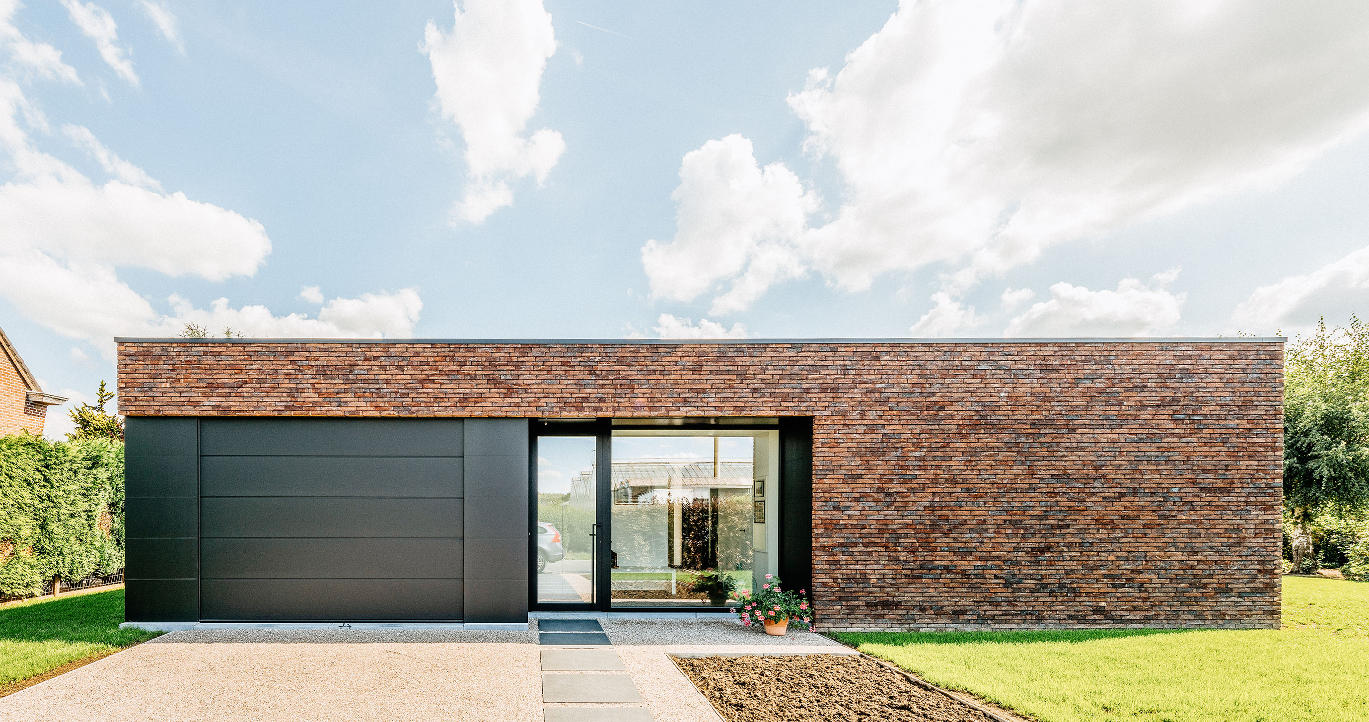Afgewerkte, strakke privéwoning met zwarte garagepoort, deuren en ramen tegen een mooie blauwe hemel.