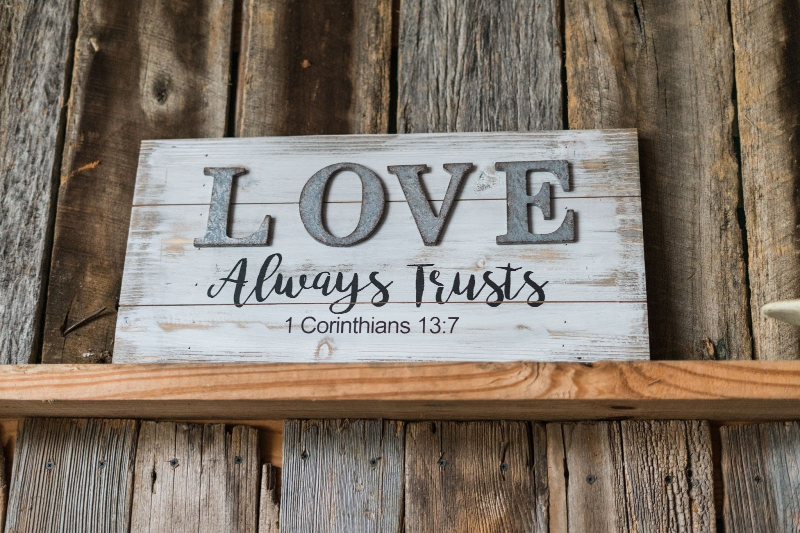 A Bible verse from 1 Corinthians 13:7 displayed in the home