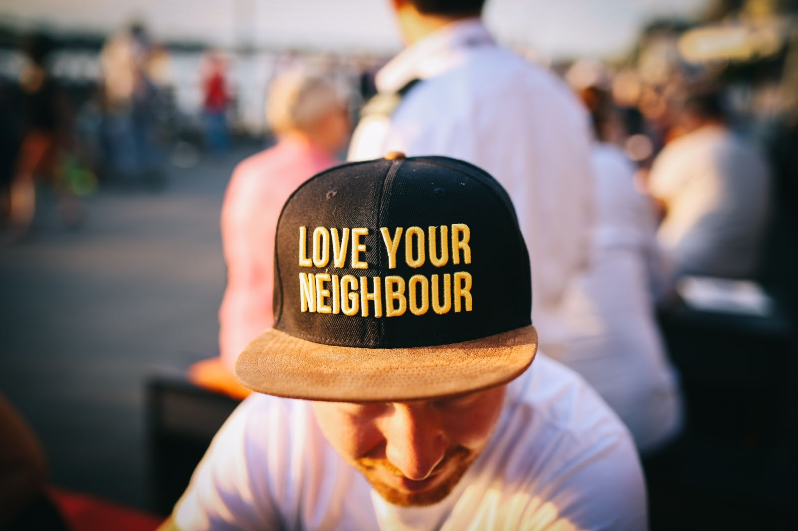 """A man wears a hat that says """"Love your neighbour"""""""