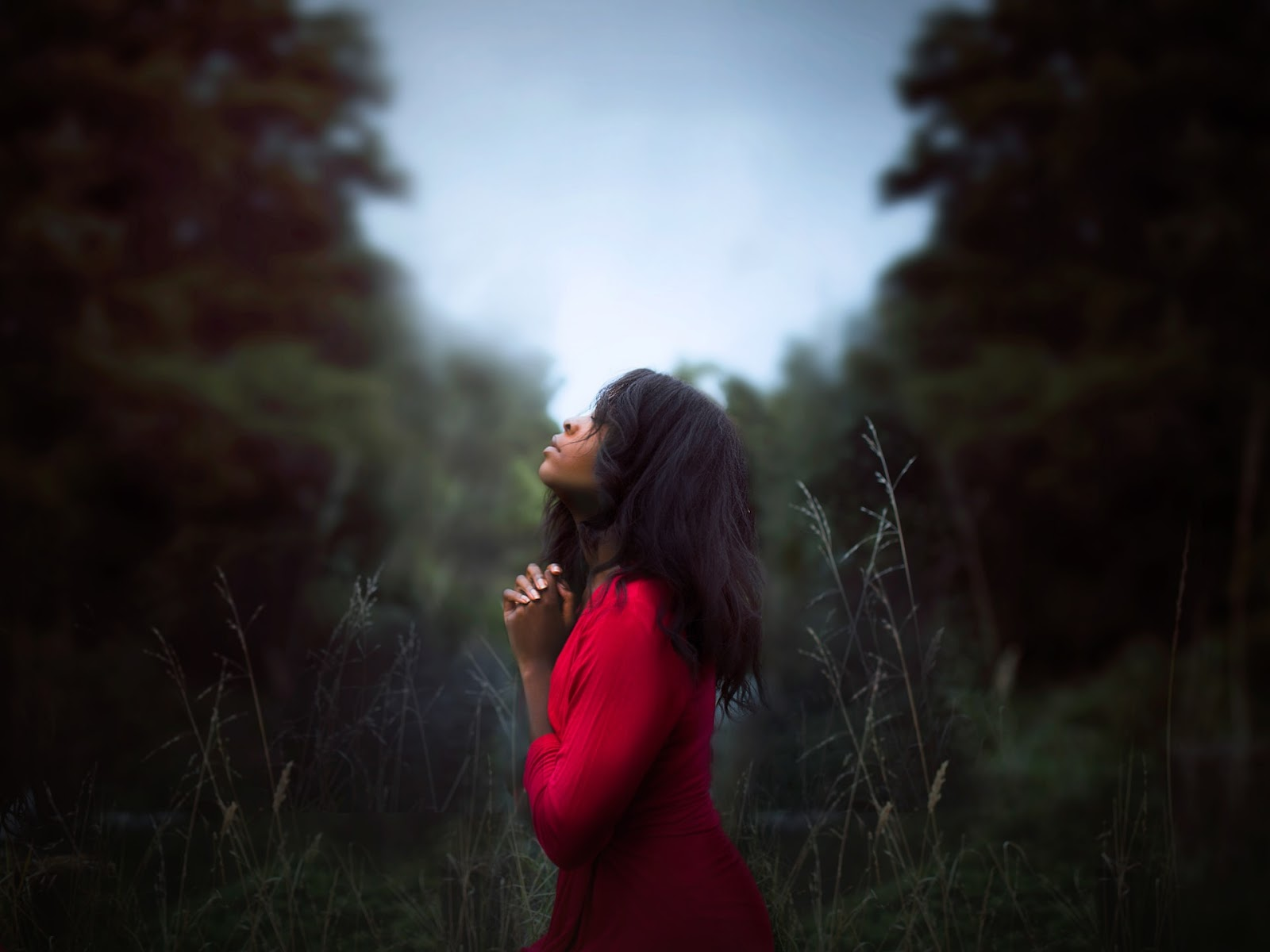 woman praying in the woods