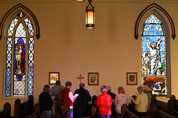 people inside a church at one of the stations of the cross