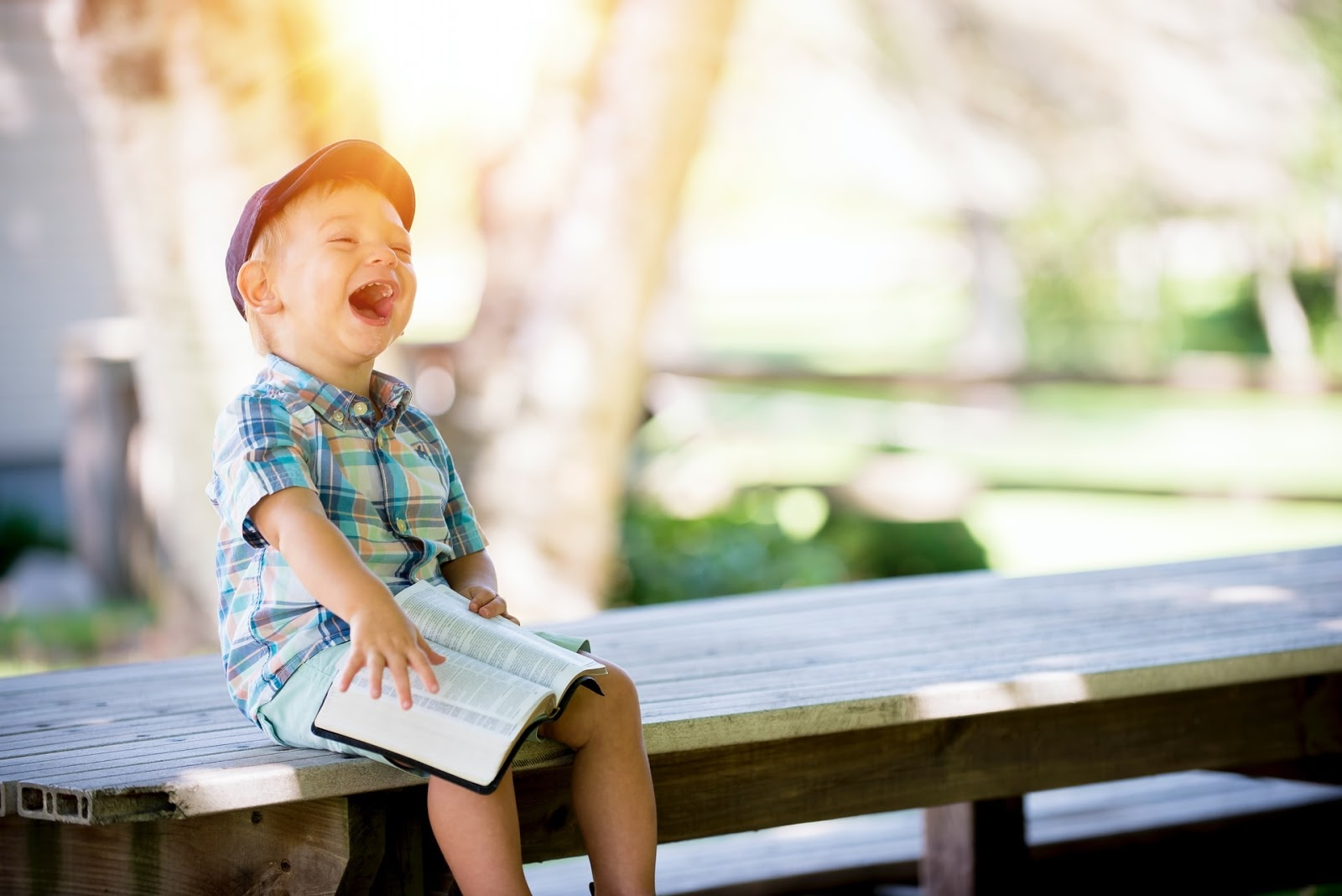 young boy laughing and sitting on a table with a bible