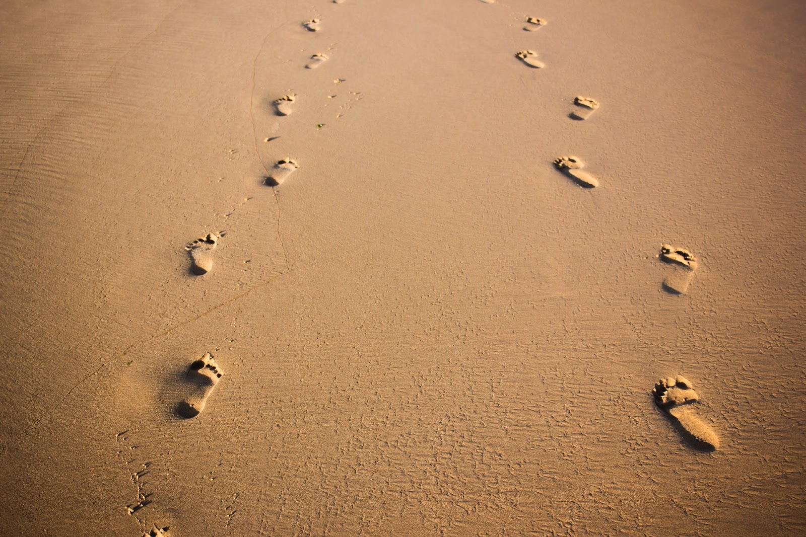 two pairs of footsteps in the sand