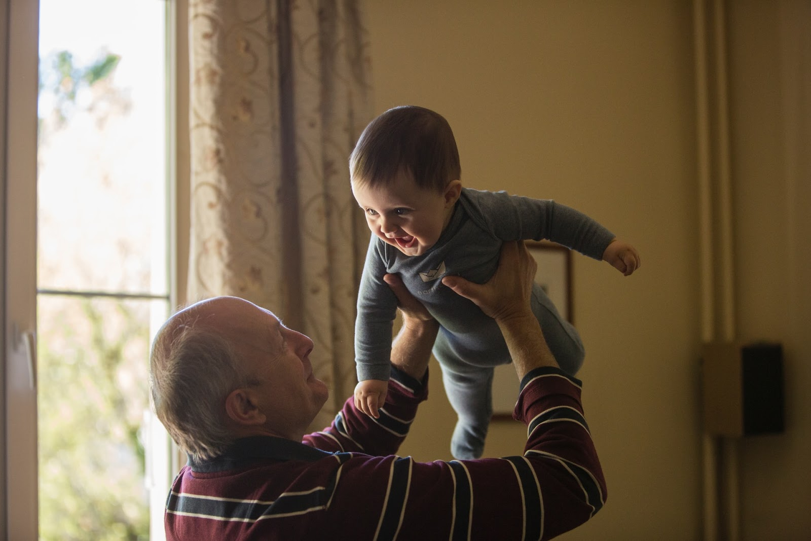 old man lifting a smiling baby into the air