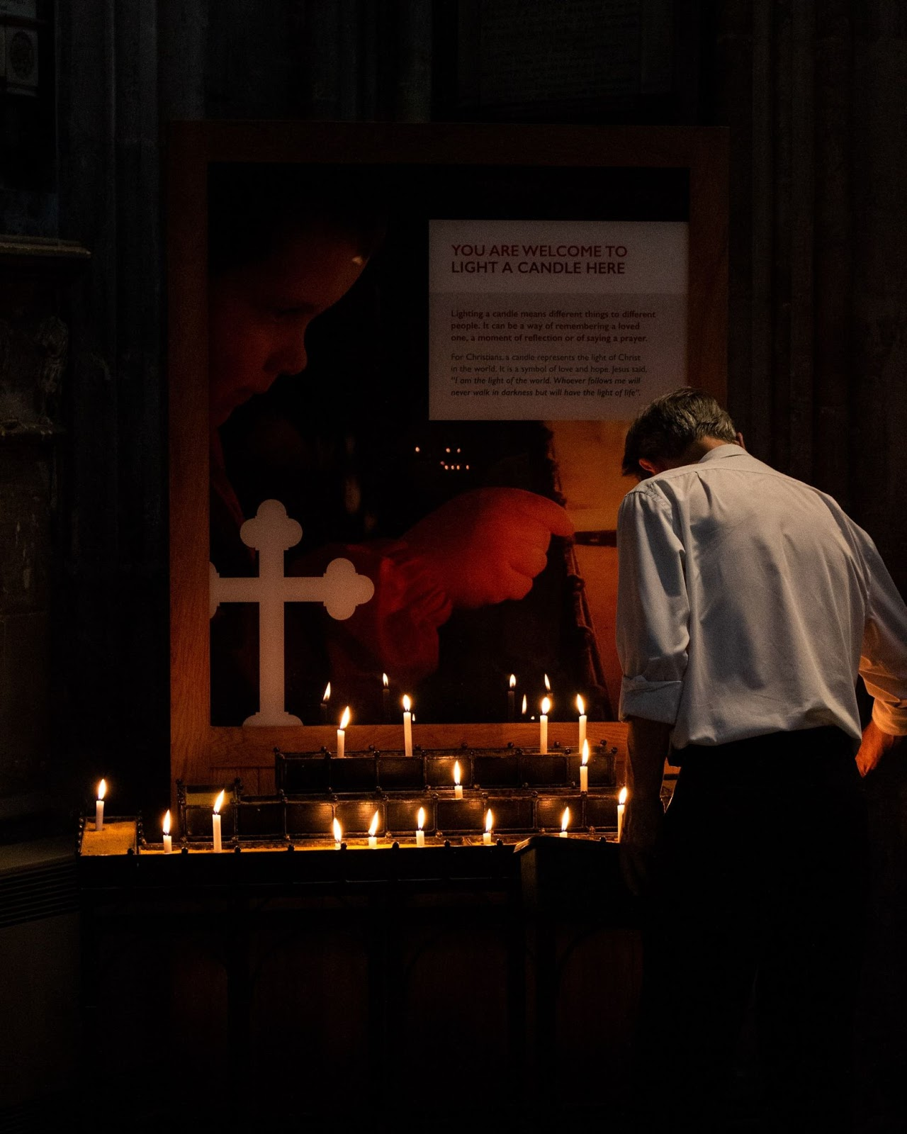 A man by an alter of candles