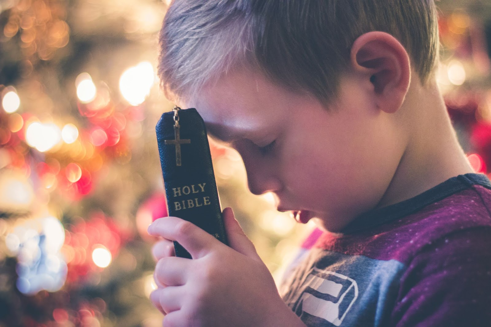 a boy pressing his head against the Bible