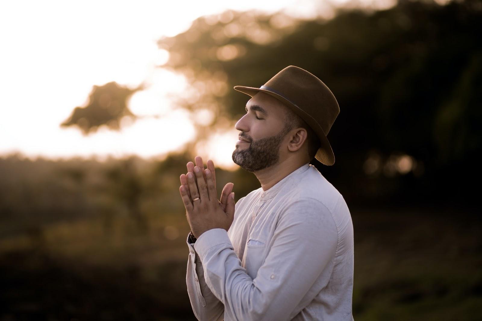 man praying in a field