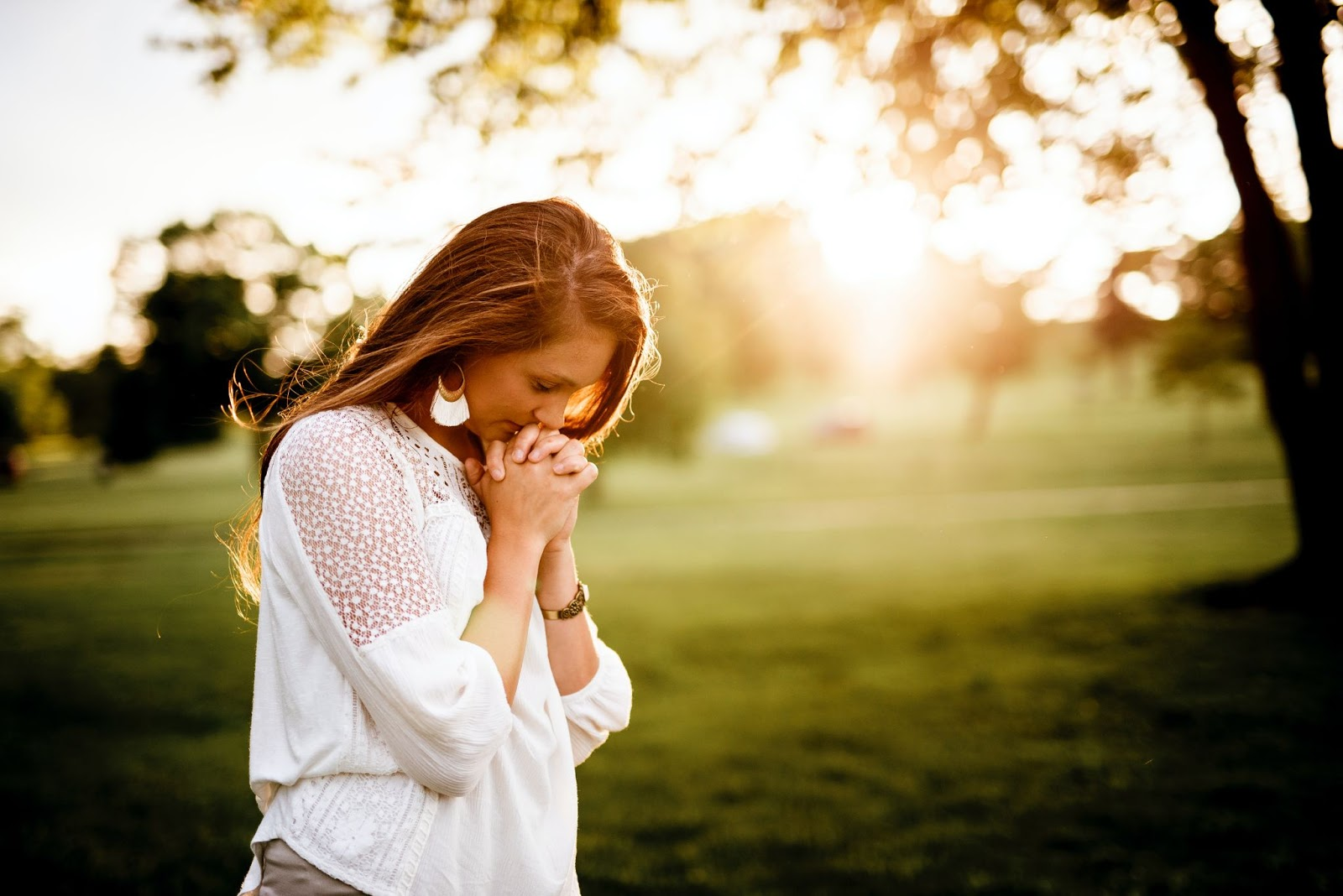 Woman praying outside with her head bowed