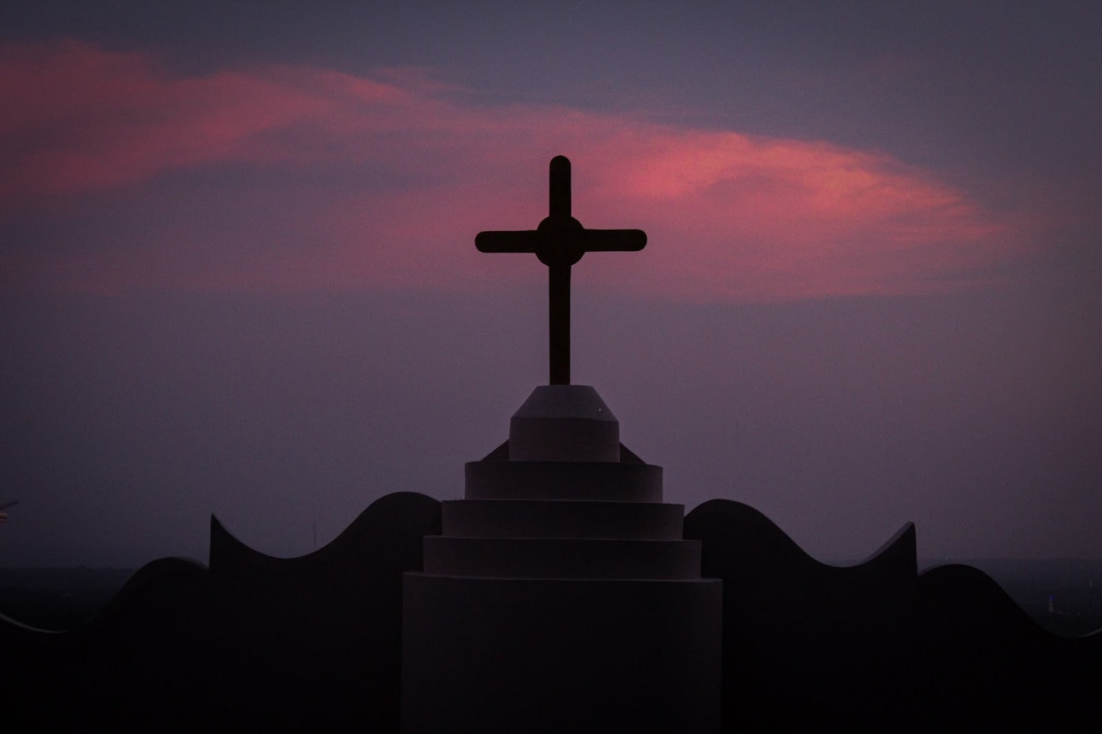 silhouette of cross on a roof at night
