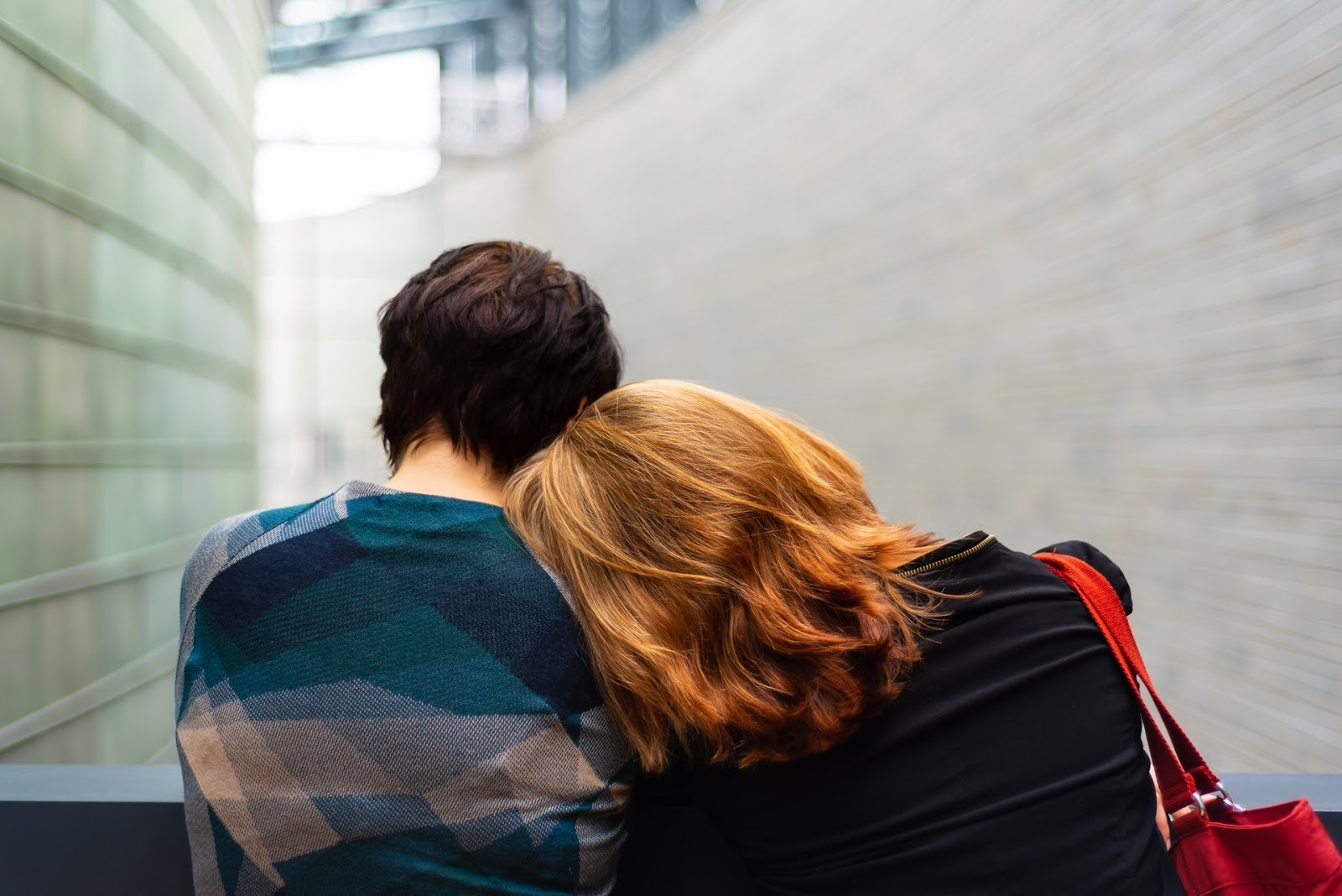 A woman with her head on another person's shoulder