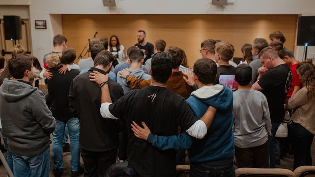 High school students engaged in classroom prayer