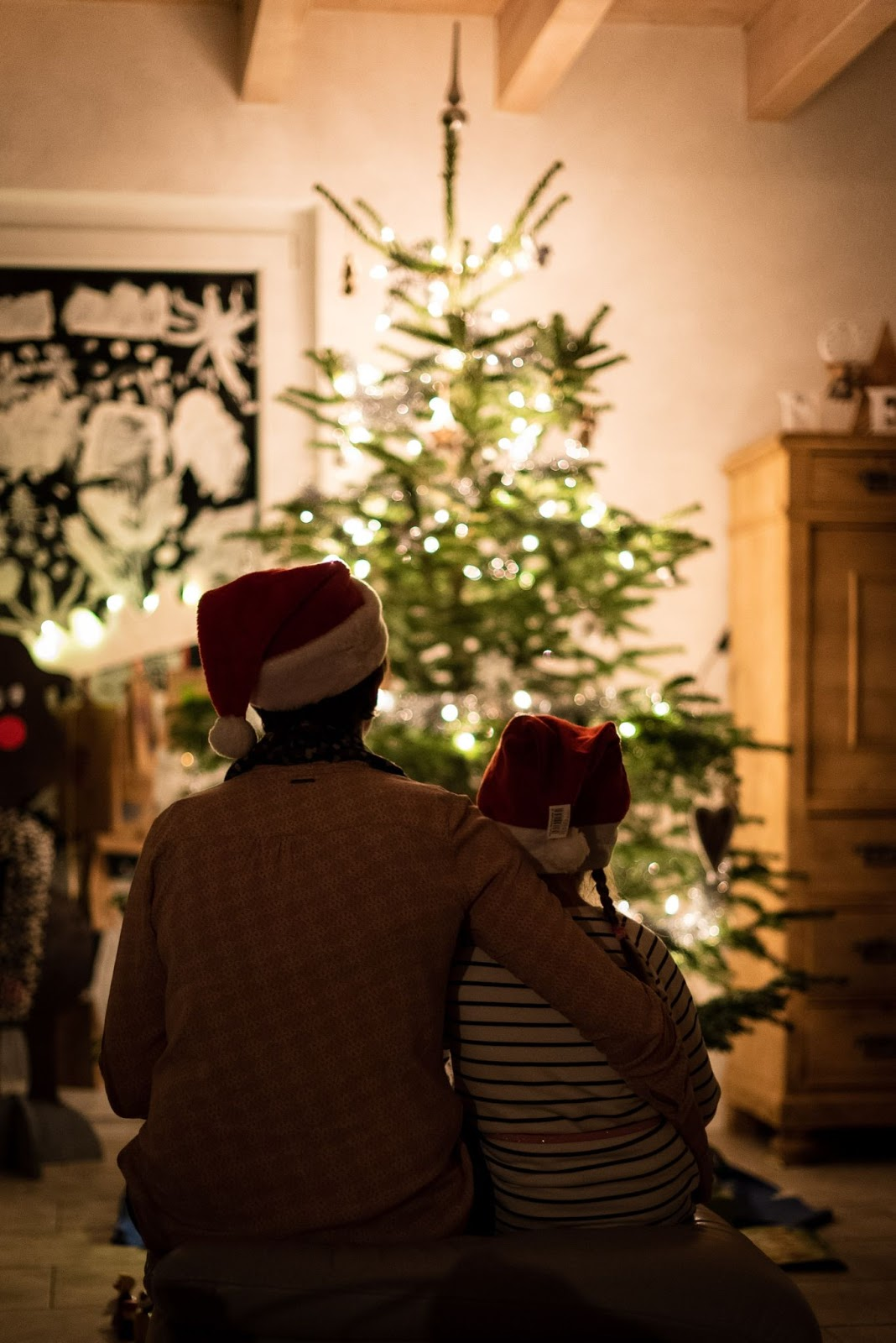 an adult and a child looking at a Christmas tree