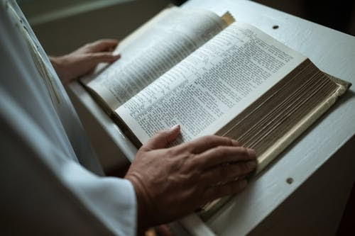 Bible sitting open on a stand with a person's hands on it.
