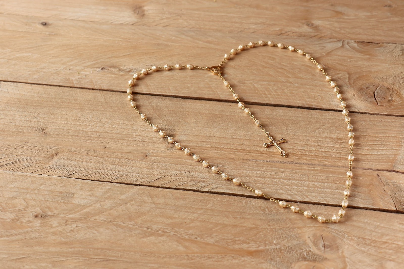 Cross necklace laid in the shape of a heart