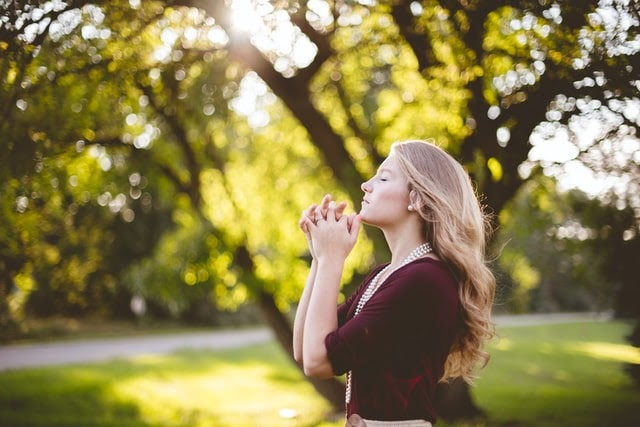 Young woman hands clasped in prayer
