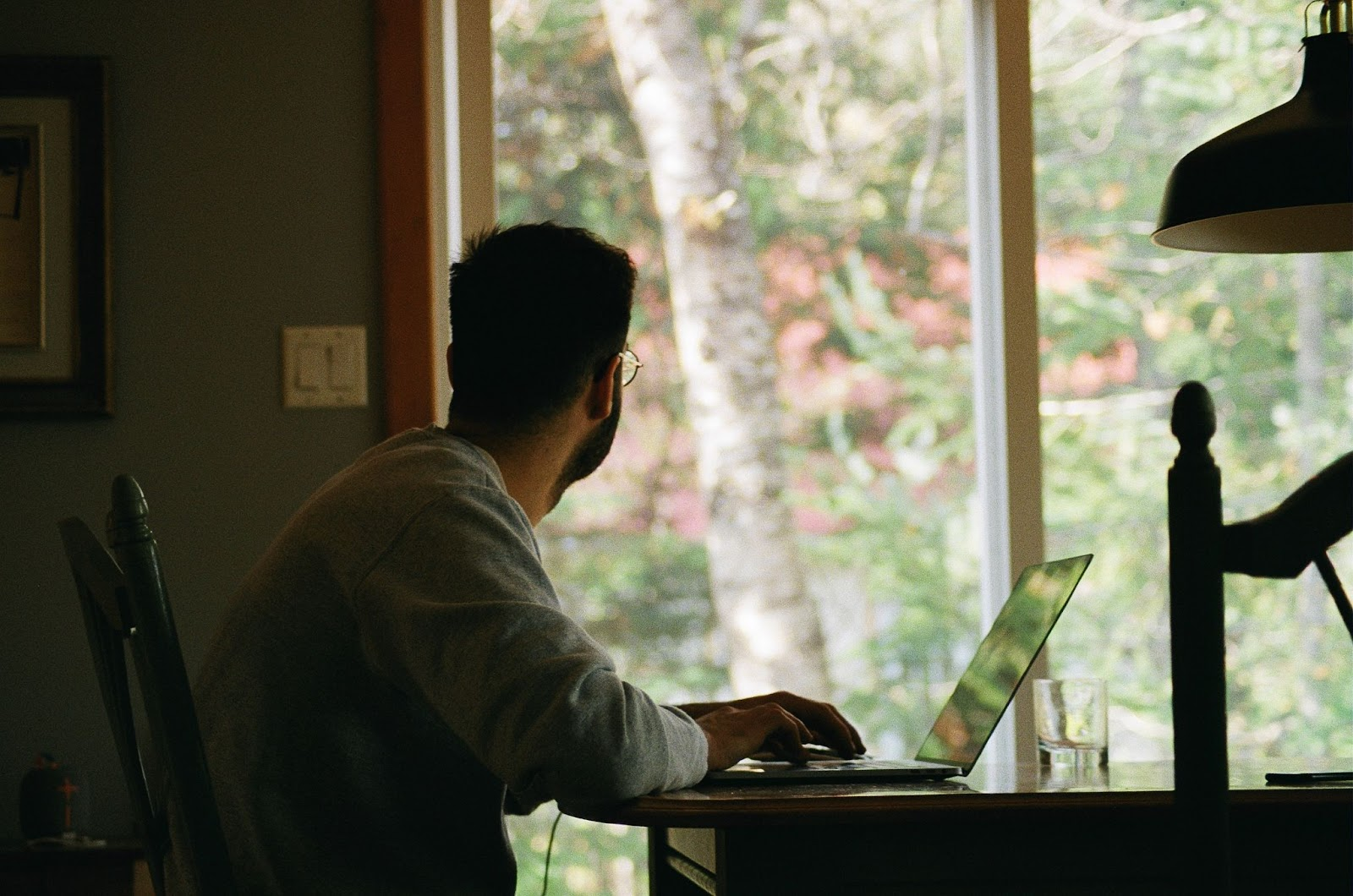 Man working at computer and looking out window.